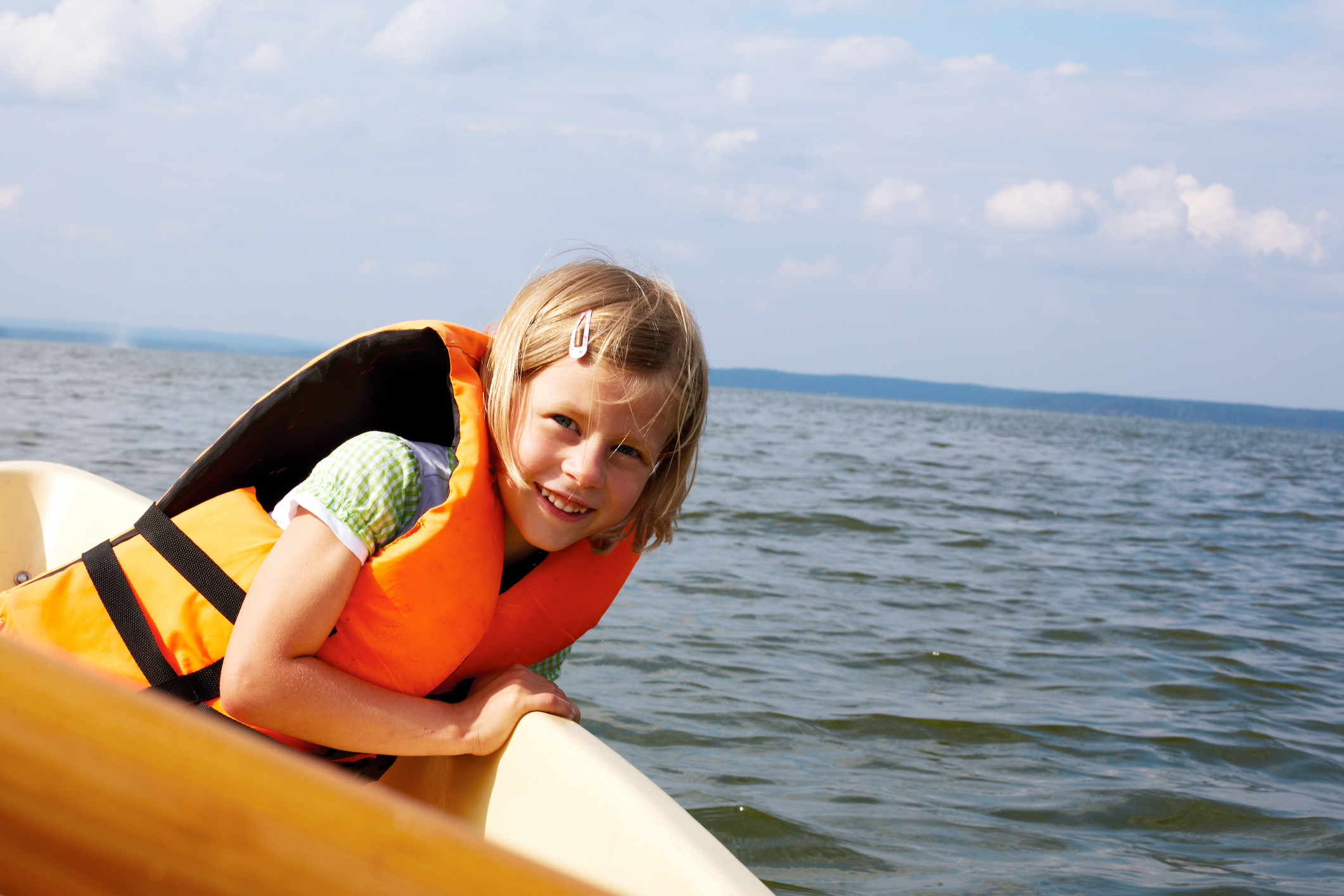 little girl dressed in life vest in a boat floats