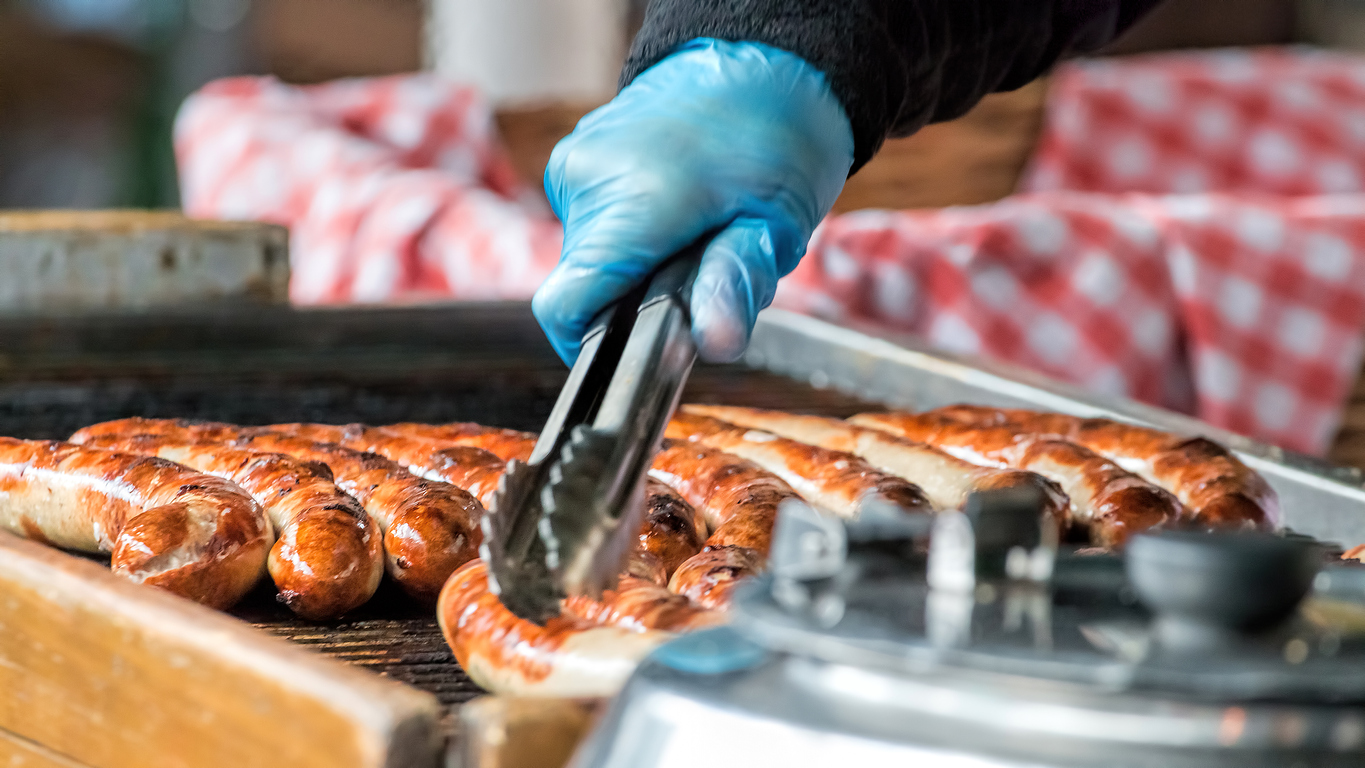 Brats being cooked on a grill at a temporary food booth.