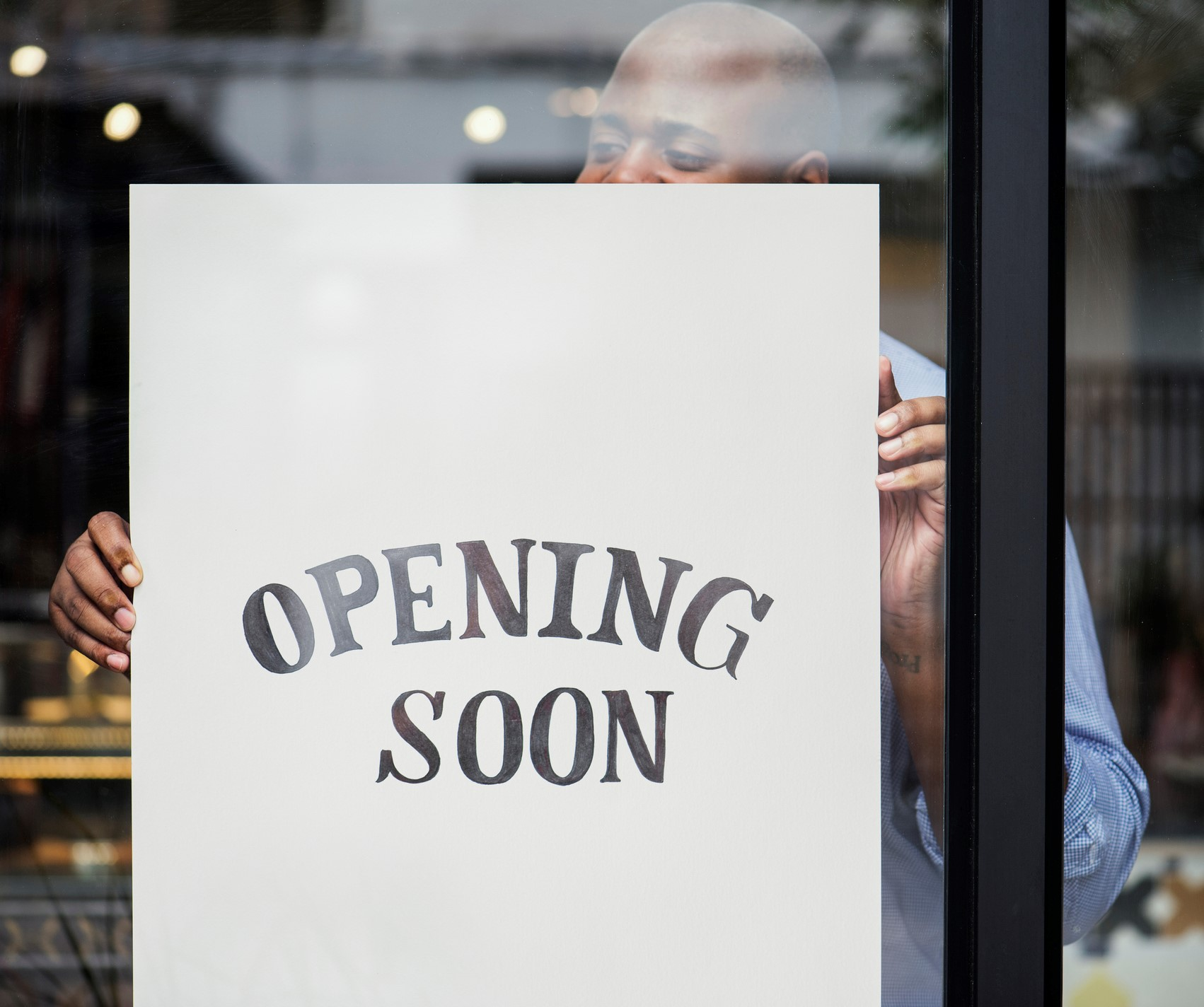 Business owner putting an Opening Soon sign in a window