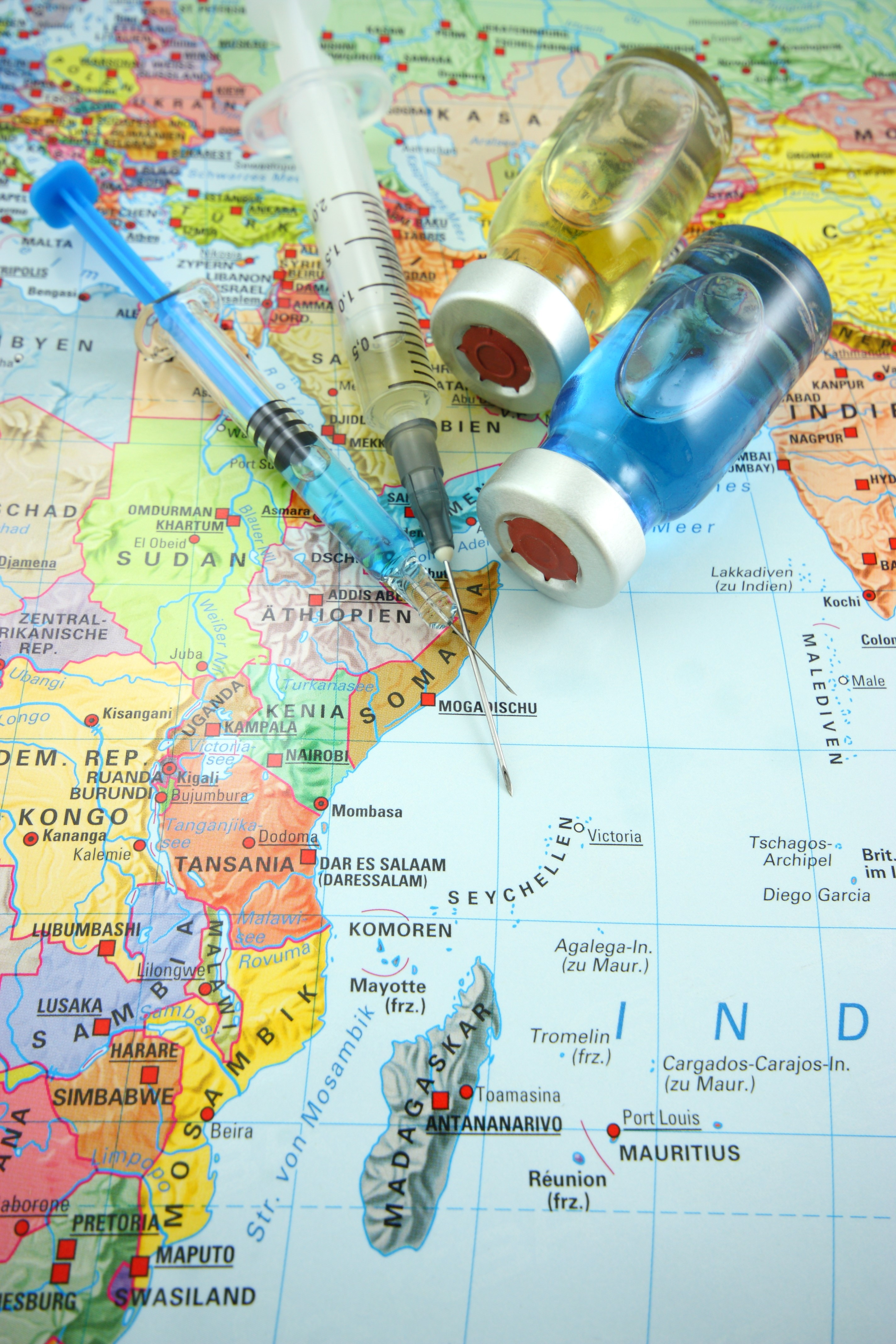 Vials of vaccines placed on top a map of Africa and India