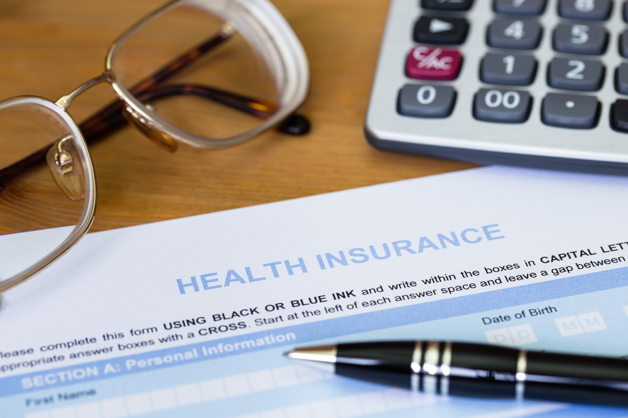 A health insurance form on a desk, with a pair of reading glasses, a calculator, and a black pen around it.
