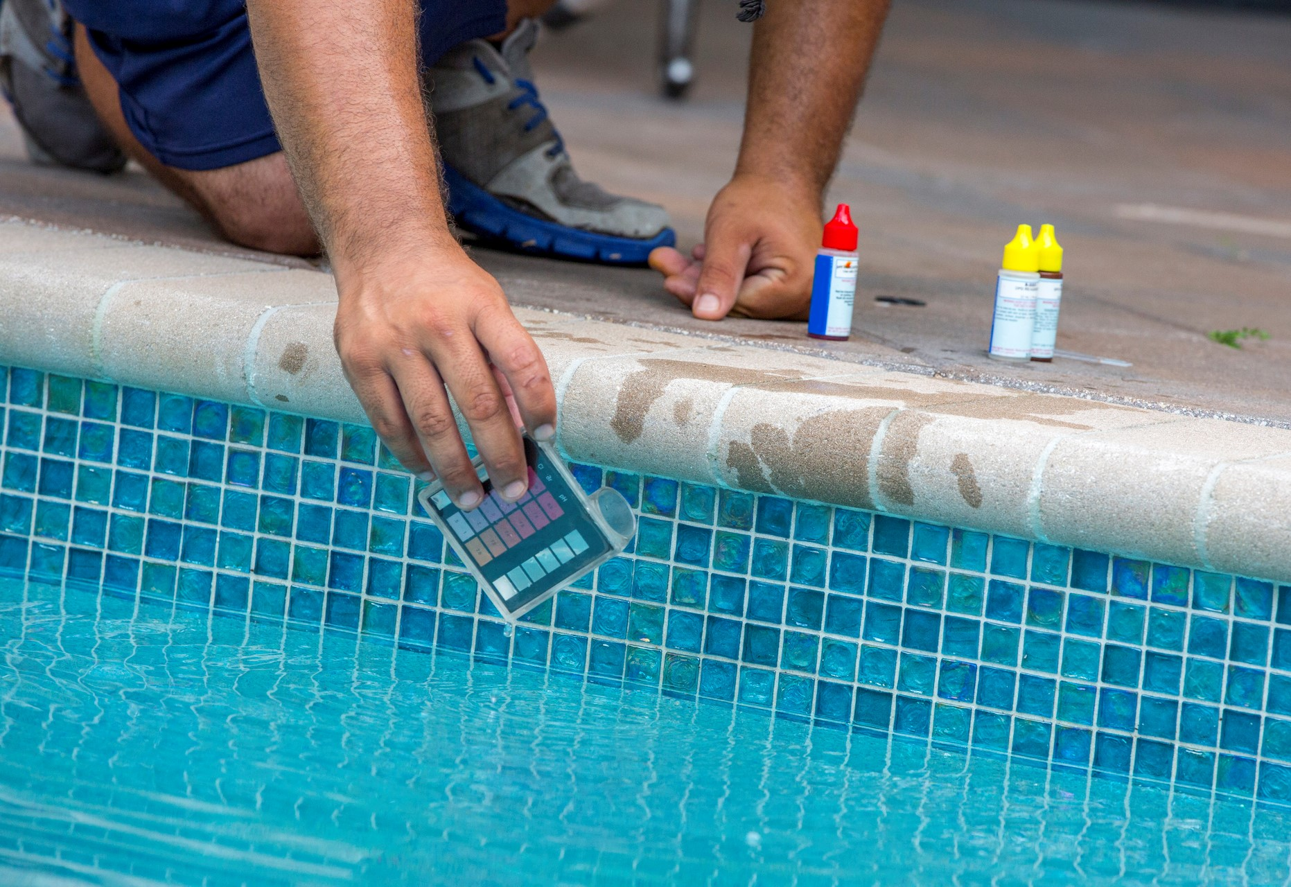 Photo of a technician taking water samples from a swimming pool to ensure public safety.